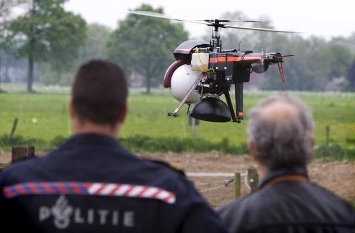 De politie ziet toe hoe de cannachopper het luchtruim kiest om de speuren naar verboden hennepproducten. foto Marcel Antonisse/ANP