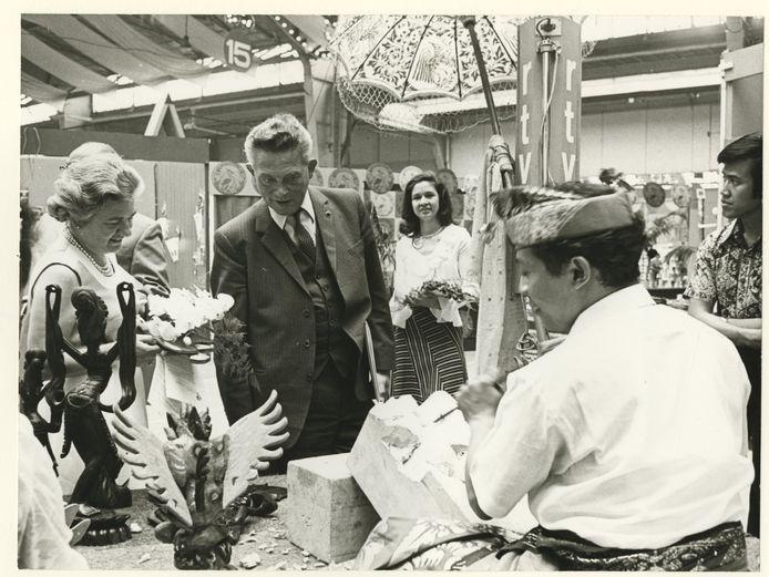 Burgemeester Vic Marijnen opent in 1973 de 15e Pasar Malam in de Houtrusthallen. Links zijn eega Miny Marijnen, op de achtergrond, met bloemstuk: Pasardirecteur Ellen Derksen,
