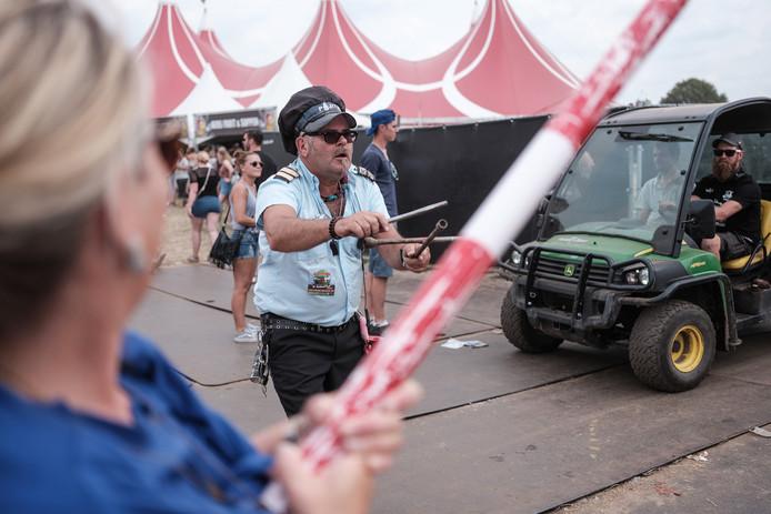 Ron van Elven, 'verkeersontregelaar' op de Zwarte Cross, helpt festivalgangers veilig oversteken.