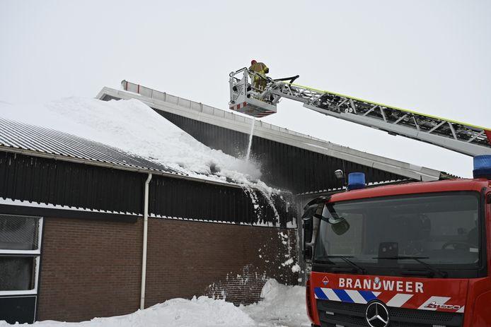 De brandweer spuit de sneeuwduin van het dak van een veehouderij in Vriezenveen.