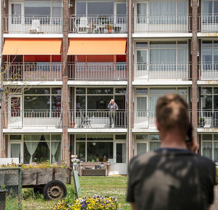 Bartele Bijma praat vanaf het balkon via de telefoon met zijn zoon Siebe. De regels in zijn woonzorgcentrum zijn 'belachelijk streng'. Beeld Harry Cock