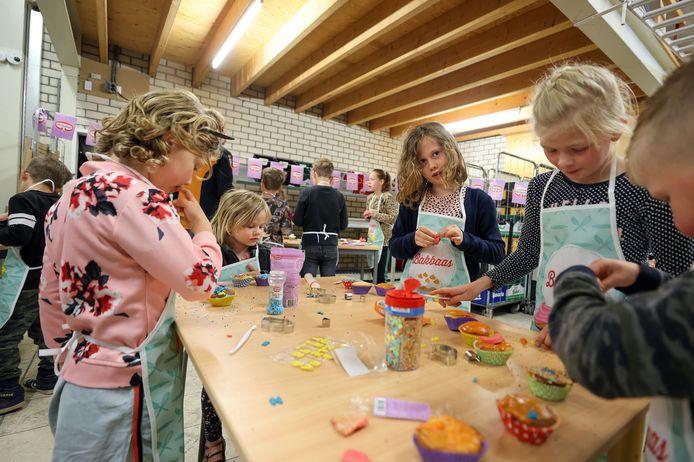 Kaat, Nan en Wies van de Ven, bezig met  cupcakes versieren én proeven.