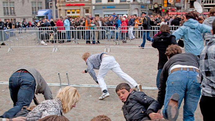 Bezoekers van de Nationale Dodenherdenking op de Dam in Amsterdam rennen in paniek weg