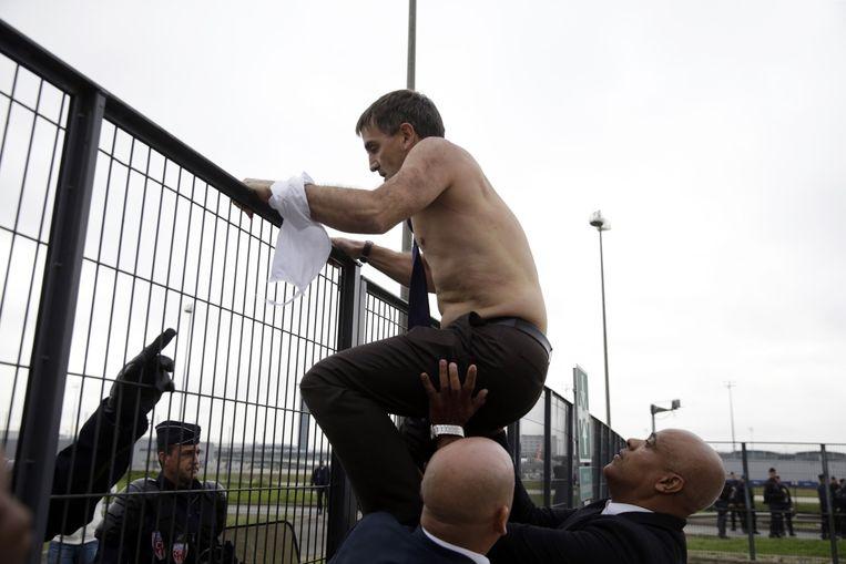 AirFrance-topman Xavier Broseta klimt over een hek om de boze medewerkers te ontvluchten. Beeld afp