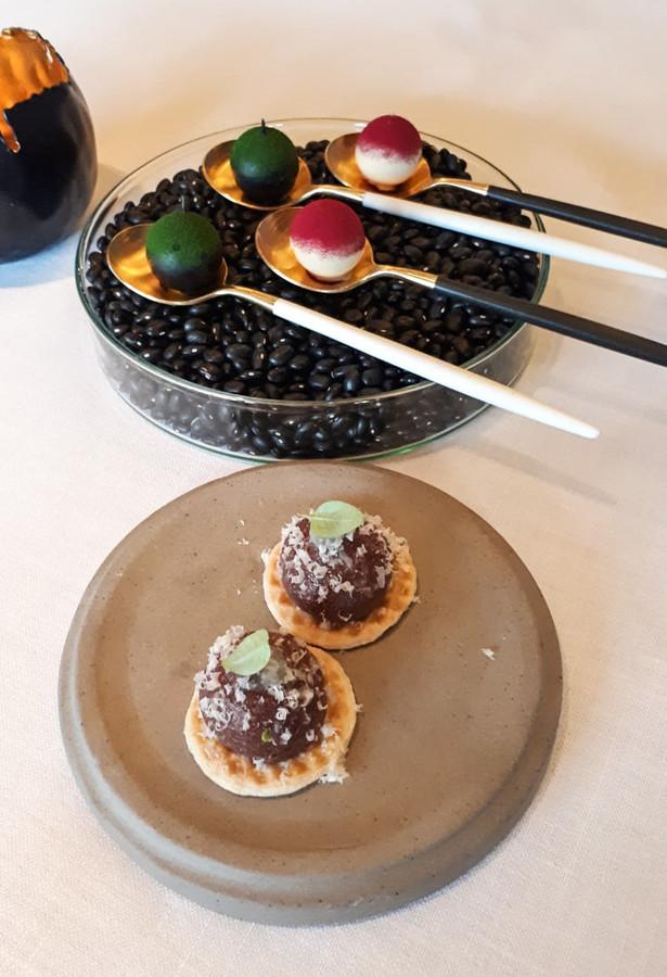 Pralines van ganzenlever, rode biet en gerookte sprot met algen. Op het toastje: bloedworst met een gel van yuzu (oosterse citrusvrucht).