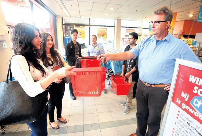 Supermarktmanager Wim de Lang geeft Sona Amanzada een rood winkelmandje.