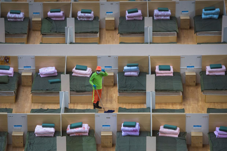 Een schoonmaker dweilt de vloer van een tijdelijk ziekenhuis met 1100 bedden in een sporthal in Wuhan.   Beeld AP