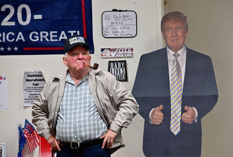 Een supporter staat bij een kartonnen Trump. Beeld AFP
