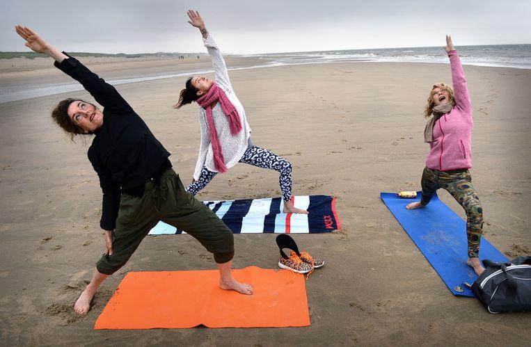 Yoga-oefeningen op het strand bij Scheveningen.  Beeld Marcel van den Bergh / de Volkskrant