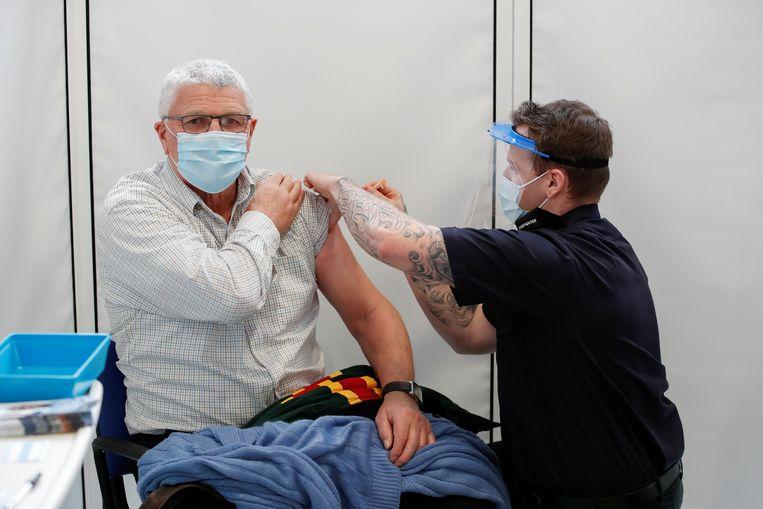 Een Brit ontvangt de prik van AstraZeneca. De Gezondheidsraad adviseert die te bewaren voor 65-minners. Of de man op de foto ouder dan 65 is, is onbekend.  Beeld REUTERS