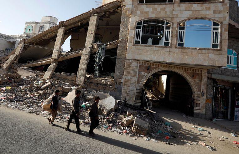 Drie jongens wandelen in de Jemenitische hoofdstad Sanaa voorbij een door de Saudi's vernield gebouw.  Beeld EPA