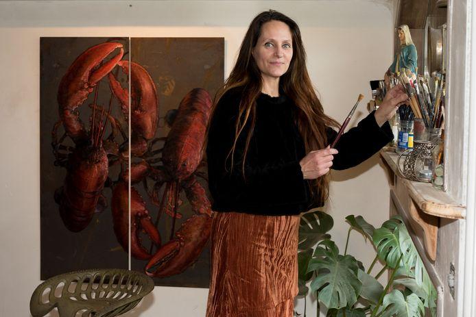 Sil van Mil heeft haar atelier verplaatst van een schuur op steenworp afstand naar de woonkamer van haar huis. Op de achtergrond het tweeluik van kreeften op verweerd plaatstaal.