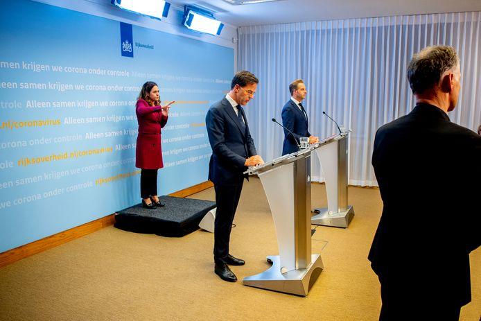 Premier Mark Rutte, minister Hugo de Jonge van Volksgezondheid, Welzijn en Sport en gebarentolk Irma Sluis bij de laatste persconferentie in Den Haag.