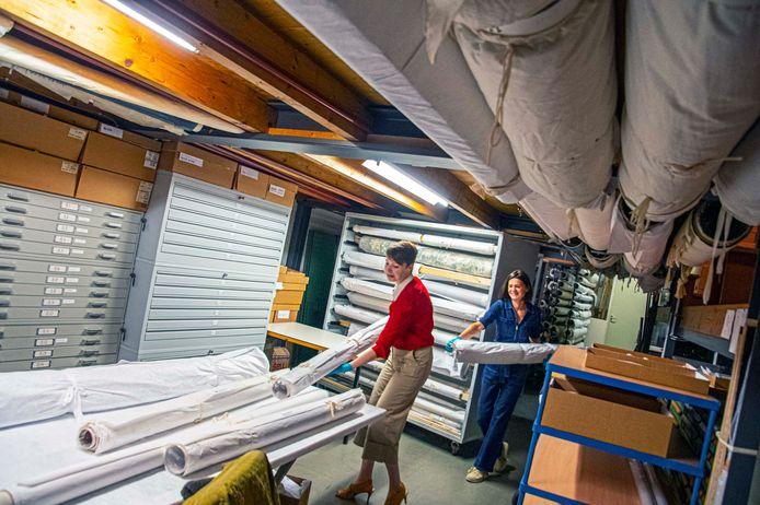 Elles van Vegchel  (links) en medewerker Rosalie Swagemakers in het overvolle depot van het Textielmuseum.