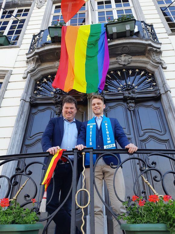 Burgemeester Anthuenis en finalist Mister Gay Belgium Matthias De Roover samen voor de regenboogvlag.