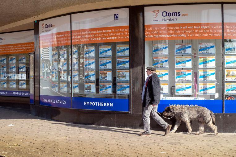 In de vitrine van een makelaar in Schiedam zijn de in de verkoop staande woningen bijna allemaal al verkocht. Beeld Hollandse Hoogte / Hans van Rhoon