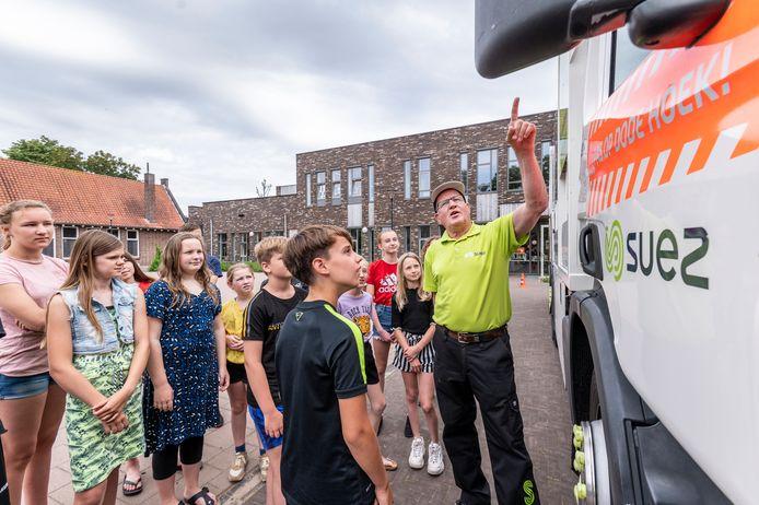 Chauffeur Harry van Tergouw van afval- en recyclingbedrijf SUEZ Nederland vertelt schoolkinderen in Odiliapeel over veiligheid rond de vrachtwagen.    .  Dodehoekproject met vrachtauto, bij school/kindcentrum Den Dijk