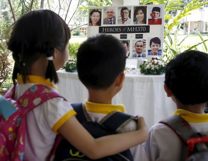 Kinderen in Kuala Lumpur kijken naar foto's van de passagiers van vermiste passagiers van MH370
