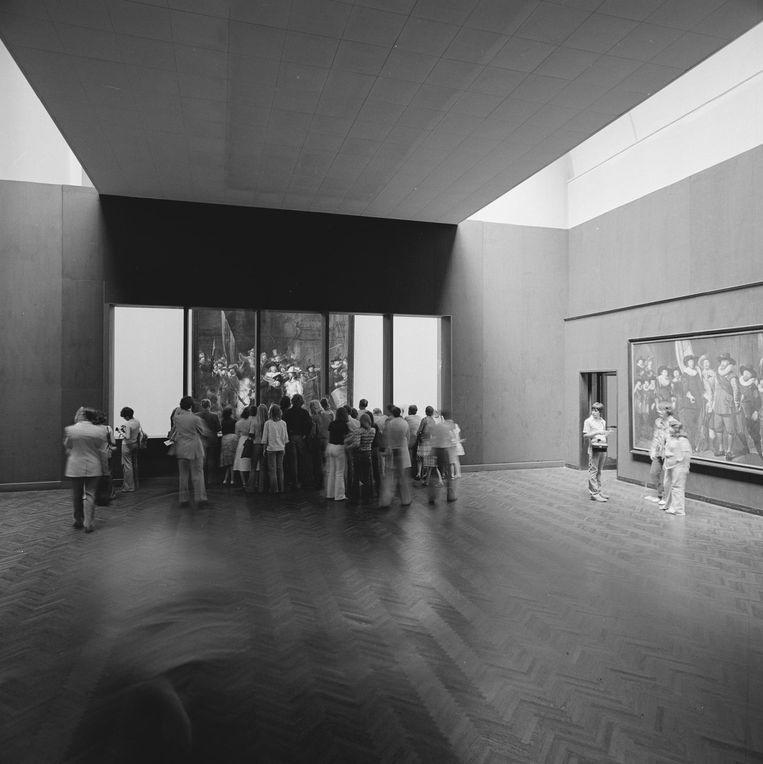 Bezoekers bekijken de voortgang van de restauratie van De Nachtwacht door de ramen van de tijdelijke studio in het Rijksmuseum, 1975-76. Beeld Rijksmuseum