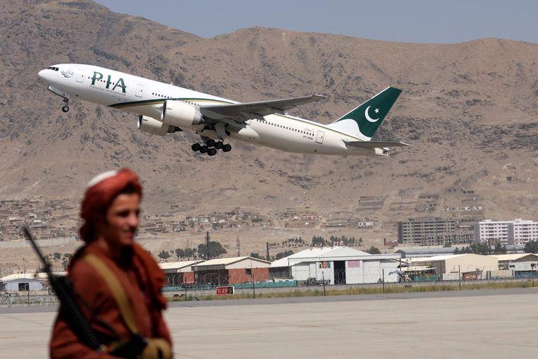 Een talibanstrijder op het vliegveld van Kaboel, waar Pakistan weer lijnvluchten heeft hervat.  Beeld AFP