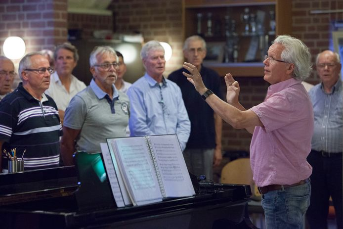 Dirigent Emile Engel aan het werk bij het Warnsvelds Mannenkoor in de pre-coronatijd. In de nieuwe setting moeten koorleden waarschijnlijk op drie meter afstand van elkaar staan.