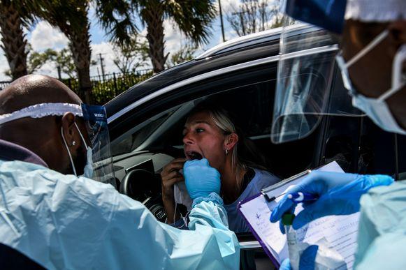 In Miami wordt een vrouw getest door medisch personeel in een drive-through.