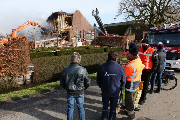 Mensen kijken toe hoe de oude woonboerderij na een verwoestende brand uit elkaar getrokken wordt.