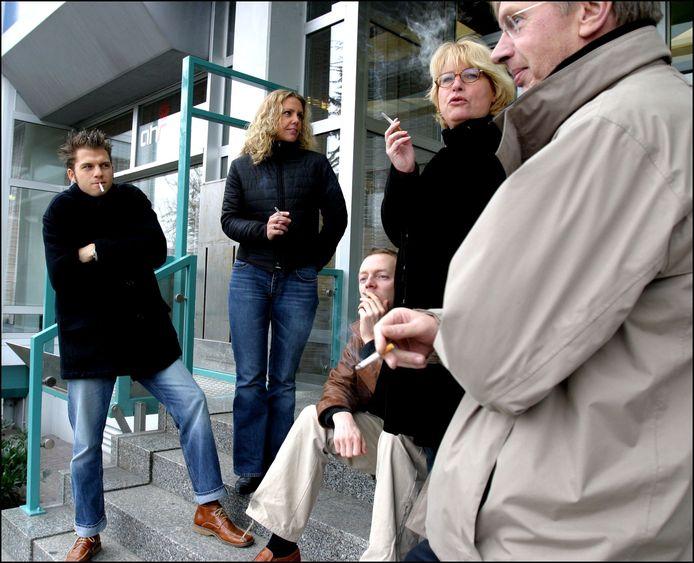 Werknemers roken buiten op straat voor de deur van hun gebouw.