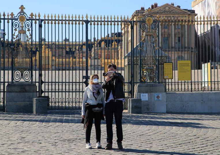 Een koppel overgebleven toeristen nemen een selfie met mondmaskers voor het paleis van Versailles. Beeld AP