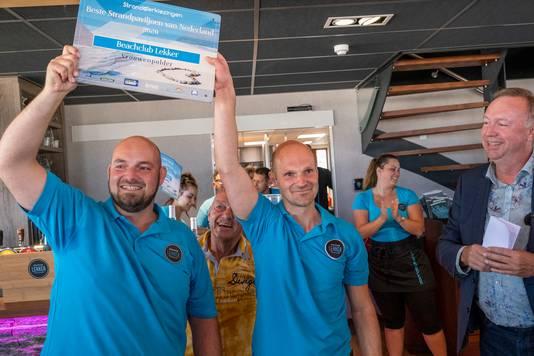 """Stephan (l) en Ricardo Soolsma zijn de trotse eigenaren van het beste strandpaviljoen van Nederland. Michel Kloeg (Koninklijke Horeca Nederland) verrast hen met die titel. ,,Hier hebben we jaren voor gewerkt."""""""