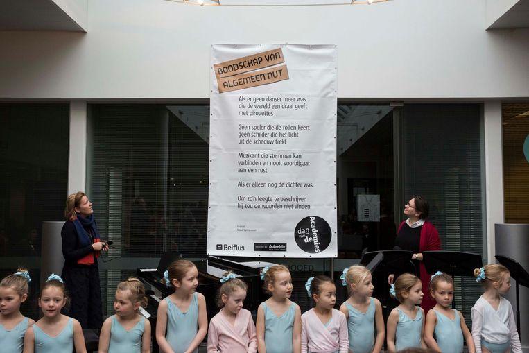 Een vijftigtal leerlingen en leerkrachten zien hoe schepen Karolien Mondelaers een nieuw gedicht van Maud Vanhauwaert onthult.