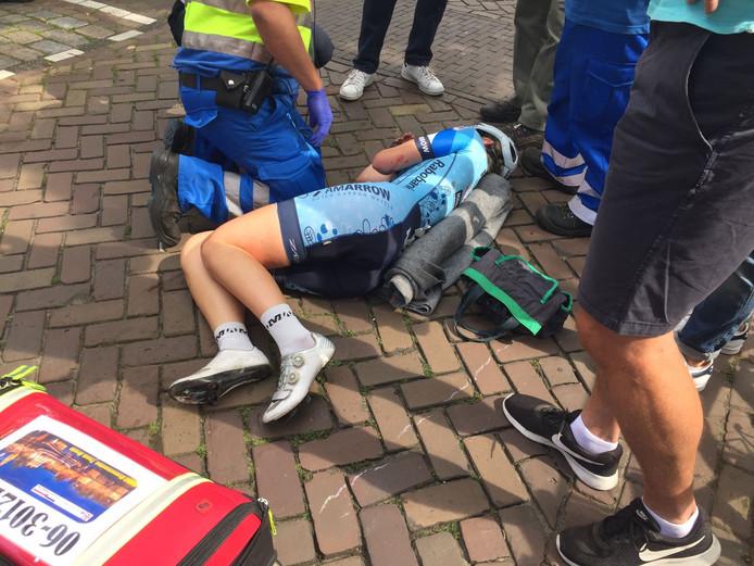 Merel Hofman wordt op de grond behandeld door een ambulancebroeder.