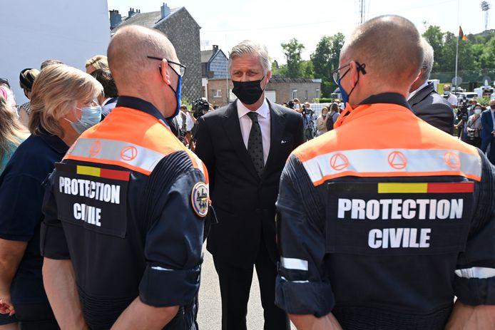 Koning Filip spreekt twee leden van de Civiele Bescherming toe bij de herdenking van de watersnoodramp, 20 juli 2021 in Verviers.