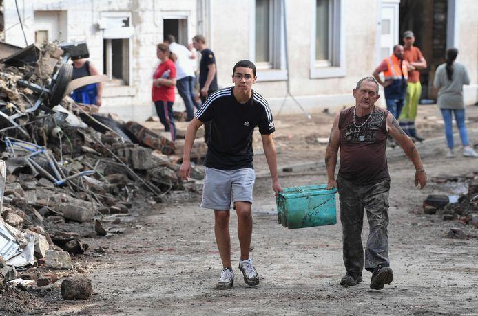 Inwoners van het Waalse Pepinster ruimen het puin op.
