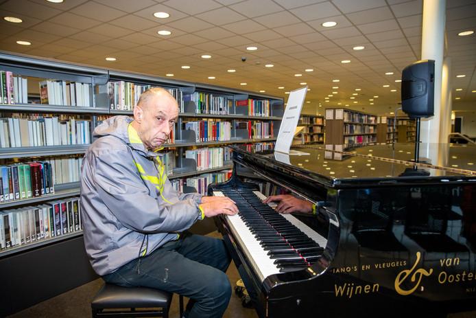 Theo Heijmans aan de piano in de bibliotheek.