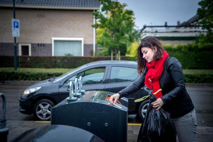 Een inwoonster brengt afval weg in Beuningen.