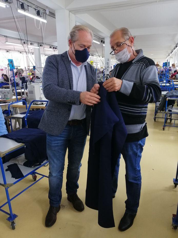 Rob Kwaspen (links) van Dutch Legends bekijkt geproduceerde werkkleding in een confectieatelier in Macedonië.