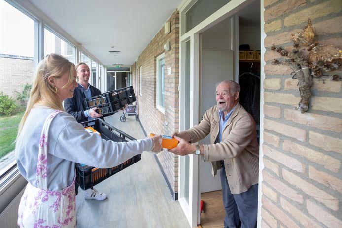 Studenten van Ceres delen tompoezen uit aan ouderen in het kader van 75 jaar vrijheid.