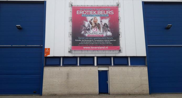 Hoog op de muur van de IJsselhallen; reclame voor de eerste editie van de erotiekbeurs in Zwolle.