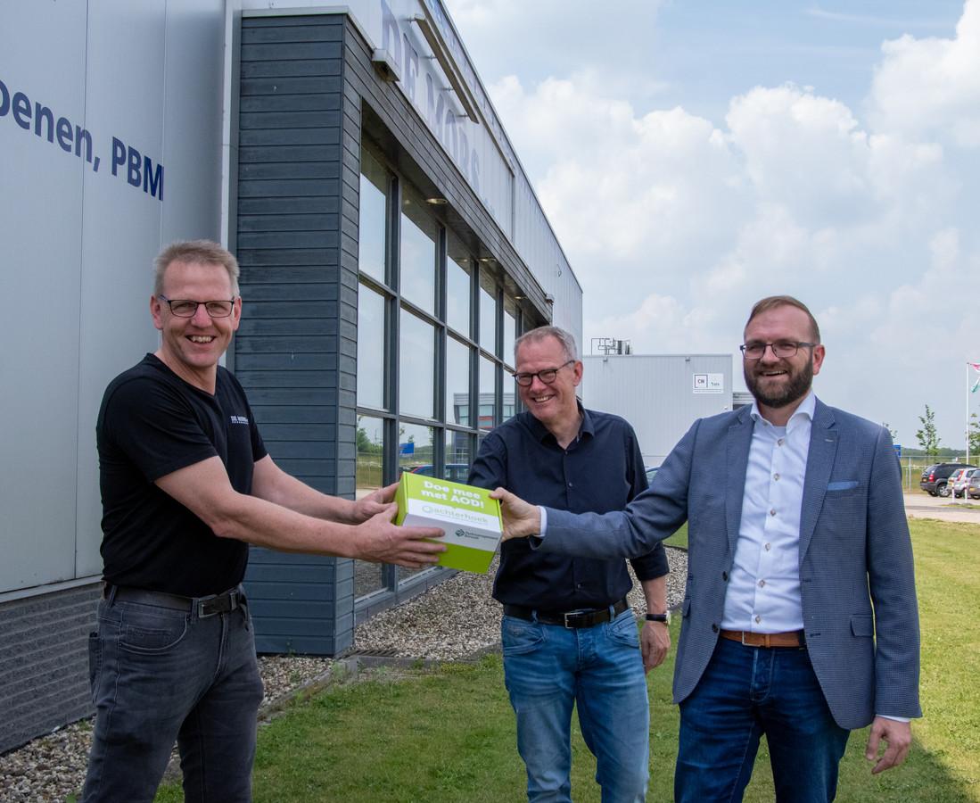 Wethouder Gerjan Teselink (rechts) en Harm ten Hoopen van de gemeente Berkelland overhandigen symbolisch het eerste 'groene' pakketje aan Bouke Walvoort (links), directeur van De Mors.