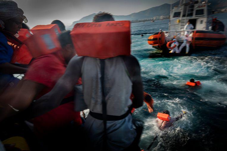 Migranten springen in het water voor de kust van Sicilië in de hoop opgepikt te worden door de Italiaanse autoriteiten. Beeld AP