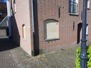 Het inmiddels dichtgetimmerde raam aan de voorkant van de woning aan de Zustersteeg in Heusden. Aan de zijkant zitten twee ramen die volgens Woonveste enkele maanden geleden zijn ingegooid.