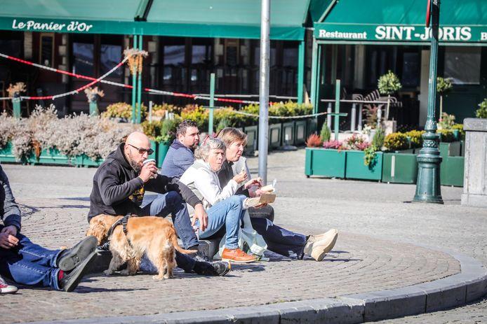 Etende mensen op de Markt in Brugge, terwijl de restaurants gesloten zijn