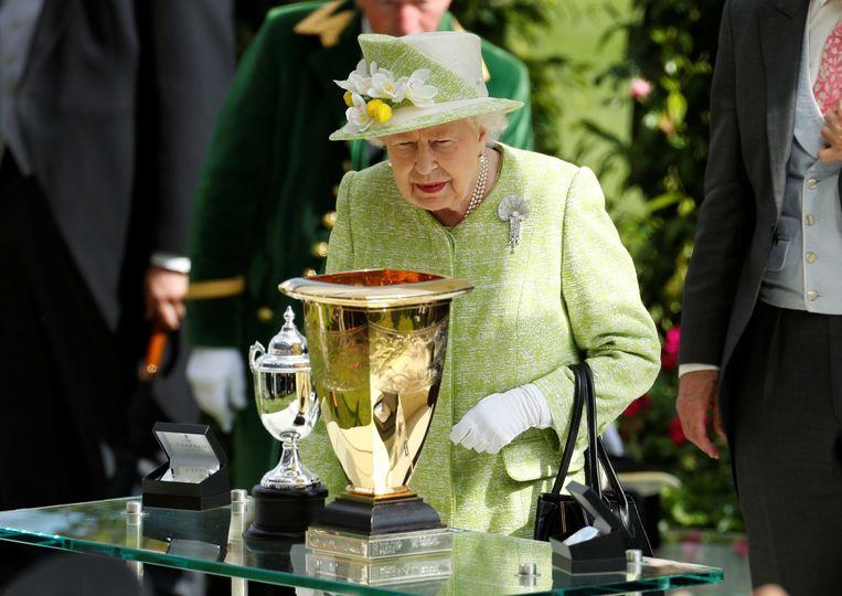 Koningin Elizabeth II inspecteert enkele bokalen bij de paardenraces van Ascot. Beeld Reuters