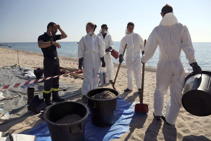 Des pompiers et des membres de la protection civile nettoient la plage de Scaffa Rossa à Solaro, le 14 juin 2021, après qu'un bateau a pollué la mer le 11 juin, au large de l'île française de Corse, en Méditerranée.