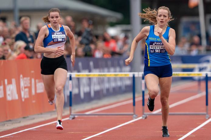 Cathelijn Peeters (r) zoeft aar nicht Silke Peeters voorbij en loopt naar het brons op de 400 meter horden bij de NK atletiek in Den Haag.