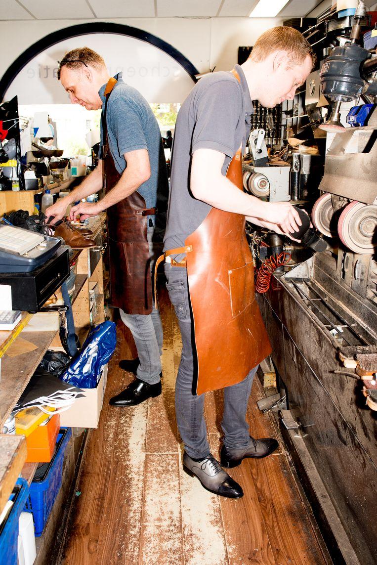Theo Frijn samen met zijn vader Onno aan het werk in hun zaak in Amsterdam-Zuid.  Beeld Marjolein van Damme
