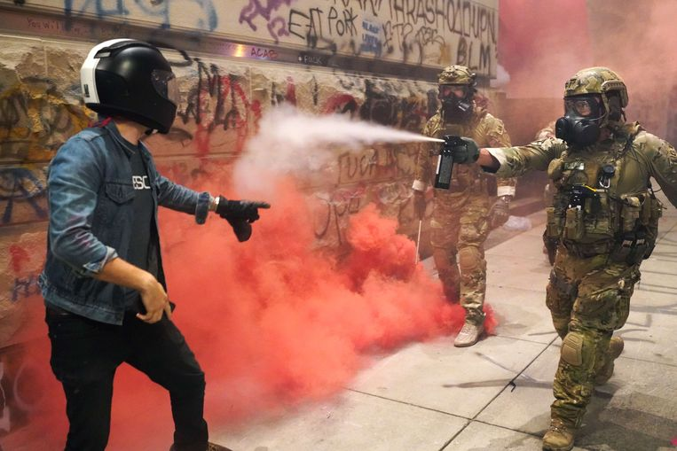 Een officier in camouflagekledij spuit pepperspray naar een demonstrant in Portland, Oregon. Beeld AFP