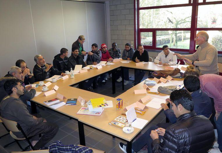 Vluchtelingen volgen een les Nederlands in Mol. Voor dat type onderwijs worden meer middelen vrijgemaakt. Beeld Vanderveken