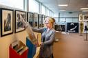 Een bezoekster van de tentoonstelling bekijkt een van de prints die te koop zijn bij Music Inspired Art. Naast haar zien we een reeks foto's van Rolling Stones-oprichter Brian Jones.